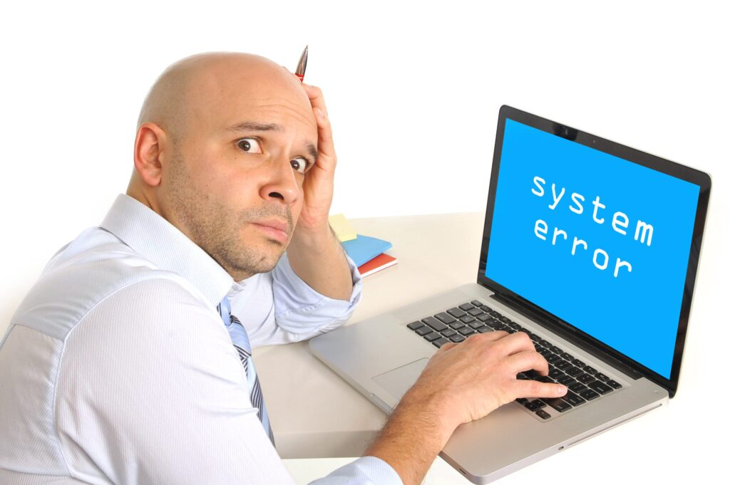 worried young business man with technical problems at computer